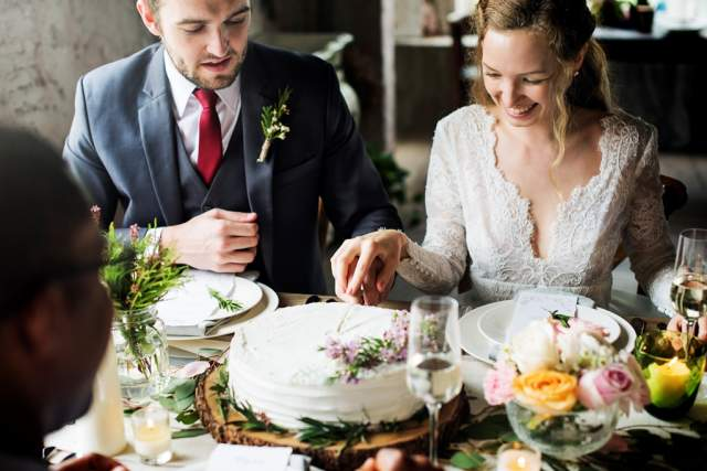 bride-and-groom-cutting-cake-on-wedding-reception