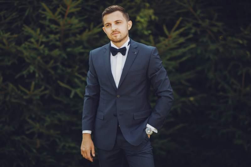 handsome-stylish-bride-blue-suit-stands-summer-park-near-bushes