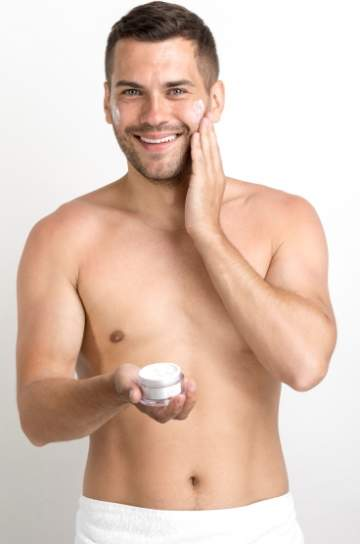 happy-young-man-using-cream-his-face-against-white-wall