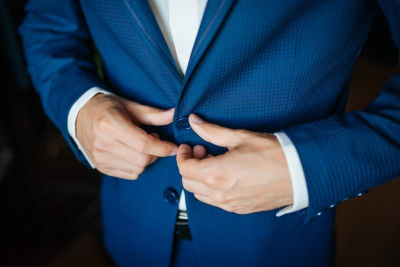 wedding-preparation-groom-buttoning-his-blue-jacket-before-wedding