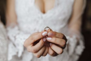 Breast of young bride dressed in wedding dress with engagement ring in hands with diamond